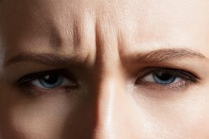 angry-face-of-a-young-woman-with-facial-wrinkles-closeup