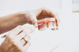 A picture of a dentist getting an implant from a denture