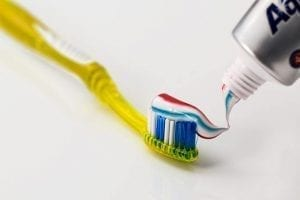A picture of a toothbrush with a lot of toothpaste against a white background