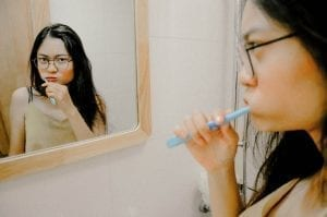 An image of a woman brushing her teeth in front of a mirror