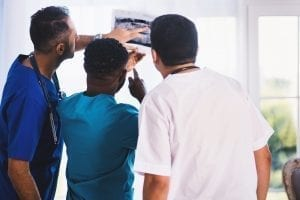 A picture of a trio of dentist examining a photo